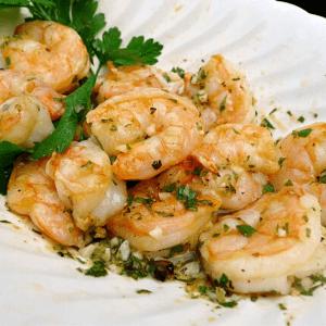 Crevettes grillées au citron, à l'ail et aux oignons dans un bol blanc avec du persil