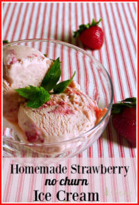 Two scoops strawberry ice cream in glass bowl with fresh strawberries on red and white ticking tablecloth.