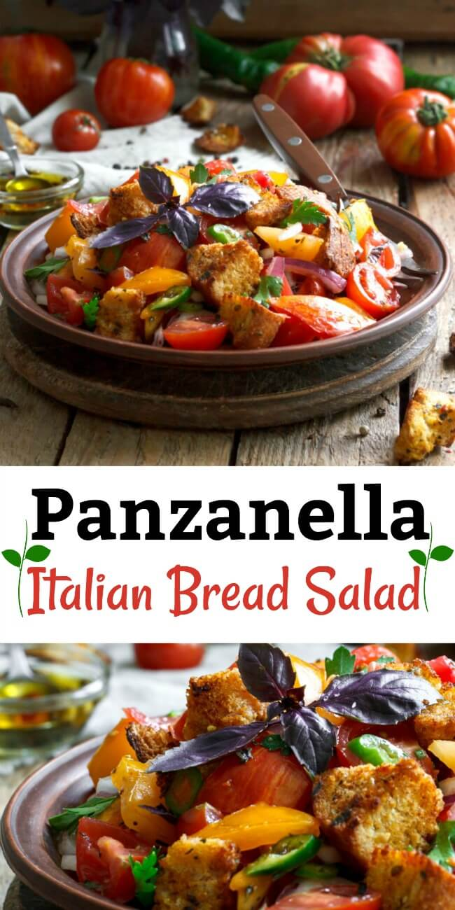 Panzanella salad a tomato and bread cubes fill a dark bowl on a wooden background.