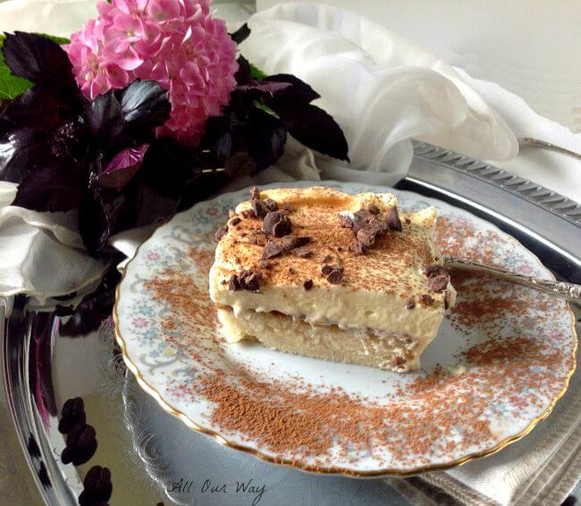 Tiramisu Cake with Zabaglione Topping on a gray flowered china plate with a silver fork on the side. A pink hydrangea blossom is in the corner. allourway.com