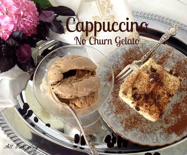 Scoop of coffee ice cream in a glass goblet with a silver spoon with a square of tiramisu cake on a tiny gray floral china plate with a silver fork all on a silver tray with coffee beans on the tray.