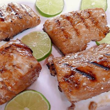 Lime marinated Mahi Mahi fillets on platter with lime slices