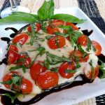 A grilled large portobello mushroom stuffed with mozzarella cheese, halved grape tomatoes, and slivers of basil set on a square white plate with a drizzle of dark balsamic vinegar all around the plate.