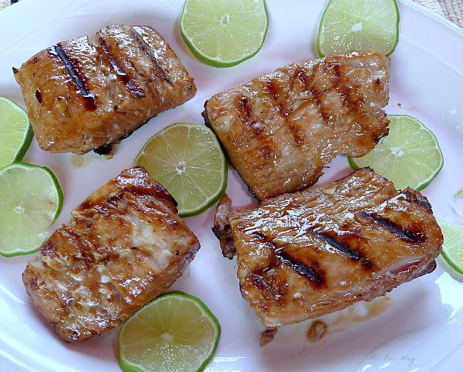 Grilled Lime Marinated Mahi Mahi with grill marks on a white plate with slices of lime surround the 4 fillets. @ allourway.com