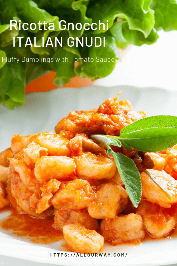 Gnocchi in tomato sauce in white bowl with green lettuce in background.