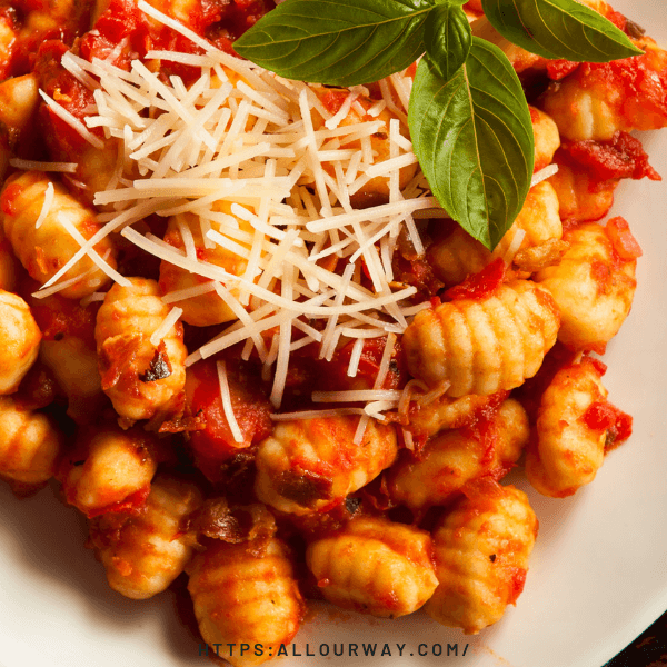 A white bowl full of gnocchi with tomato sauce a sprinkle of parmesan cheese and a sprig of basil .