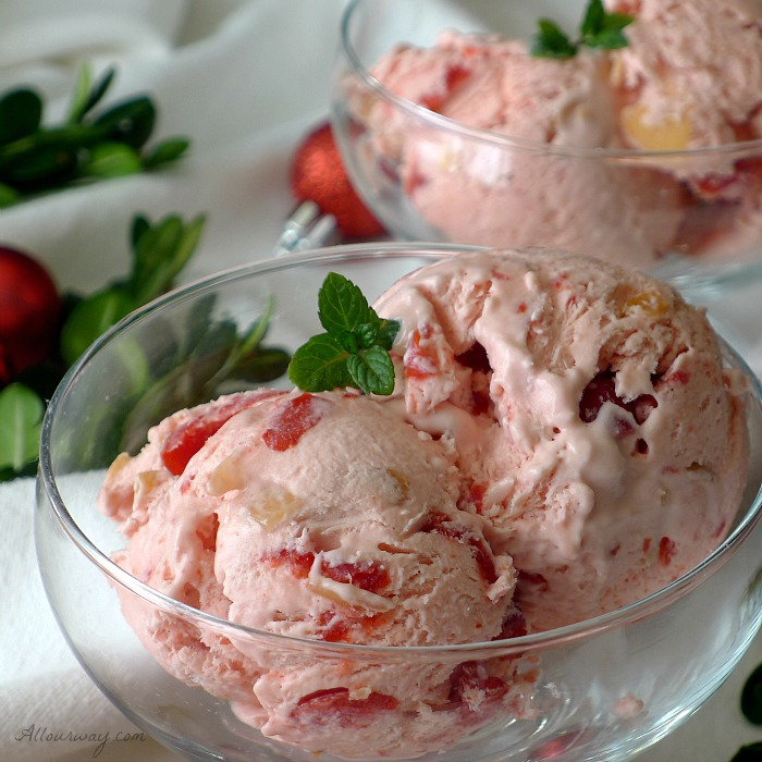 Two scoops of pink Cherry Almond Amaretto No-Churn Ice Cream in a delicate glass bowl surrounded by red mini Christmas balls and green boxwood on a white snowy background.