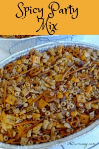 A large aluminum roasting pan filled with party mix consisting of nuts, Chex cereal, pretzels, Cheerios, and square crackers,