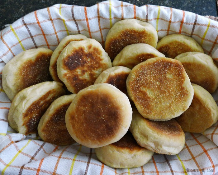 English Muffins are in an oblong basket that is lined with a brown, orange, yellow, tea towel.