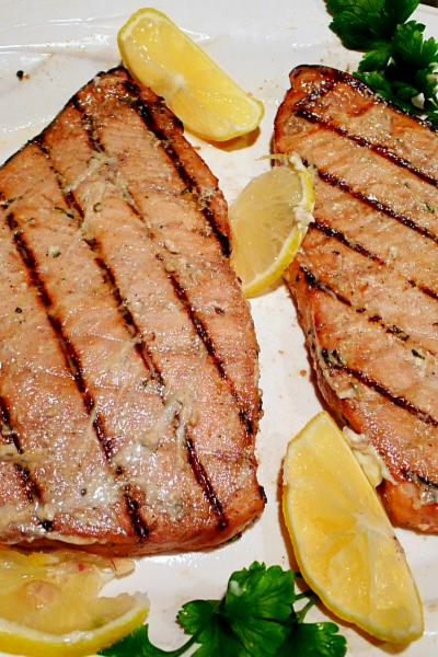 Swordfish with grill marks on white plate with lemon wedges and parsley
