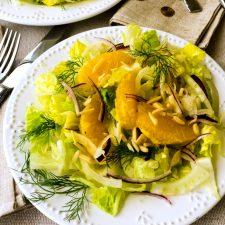 Fennel Orange Salad is a light salad with shaved fennel, sweet orange segments, slivered purple onion, and crunchy romaine and. A light citrus vinaigrette dresses the salad.