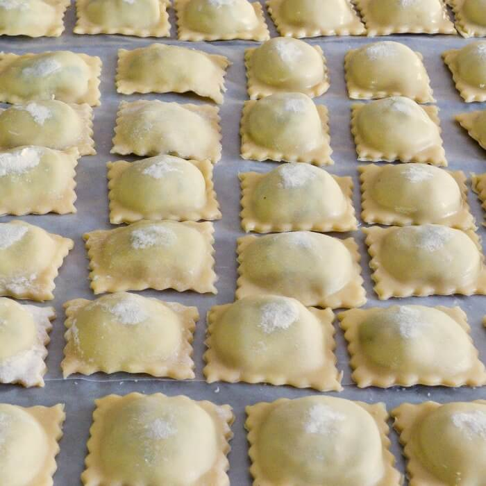 Row after row of Spinach Ricotta Beef Ravioli Filling lined up on cookie sheet ready to freeze.i