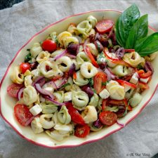 Red, Green, White colored Cheese Tortellini Salad With Sun-Dried Tomatoes a deep yellow and red bowl