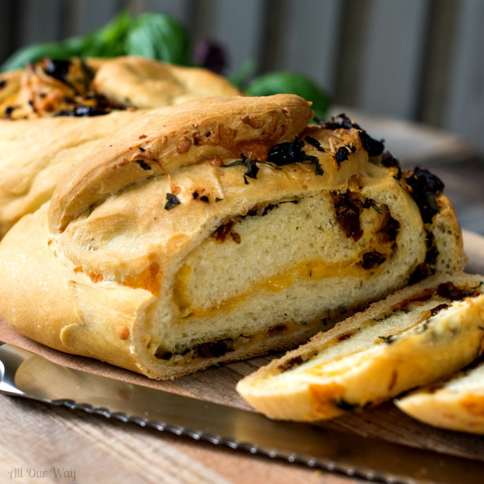 Herb cheese Swirl Pane Italiano a savory stuffed bread sliced on a wooden platter with a bread knife in front. @allourway.com