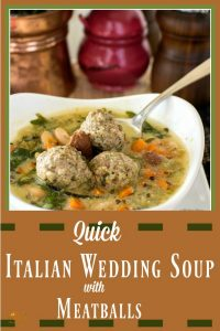 Italian Wedding soup with three meatballs in a white bowl and a purple parmesan jar in the background with a copper bucket and wood salt and pepper mills.