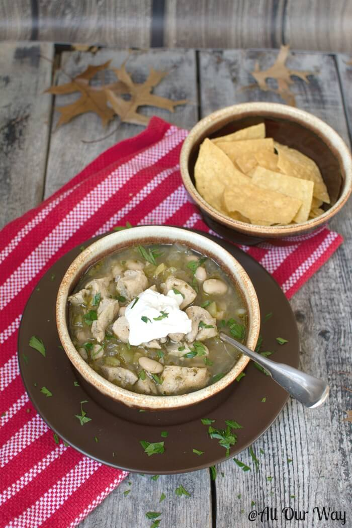 Wickedly Good Spicy White chicken Chili with lime and cilantro in brown glazed bowl with a dollop of sour cream on top. Tortilla chips in another brown bowl and they are set atop a red and white striped tea towel on rustic gray boards with brown oak leaves strewn around.