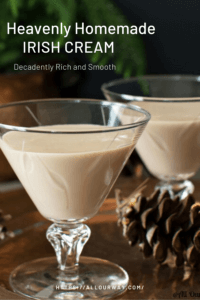 Two glasses of Irish cream Liqueur with pine cones on the table and evergreen branches in background.