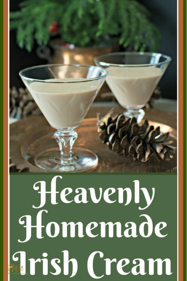 Two fluted glasses filled with homemade Irish cream after dinner drink on a copper serving tray with pine cones on the table and a Christmas tree in the background.