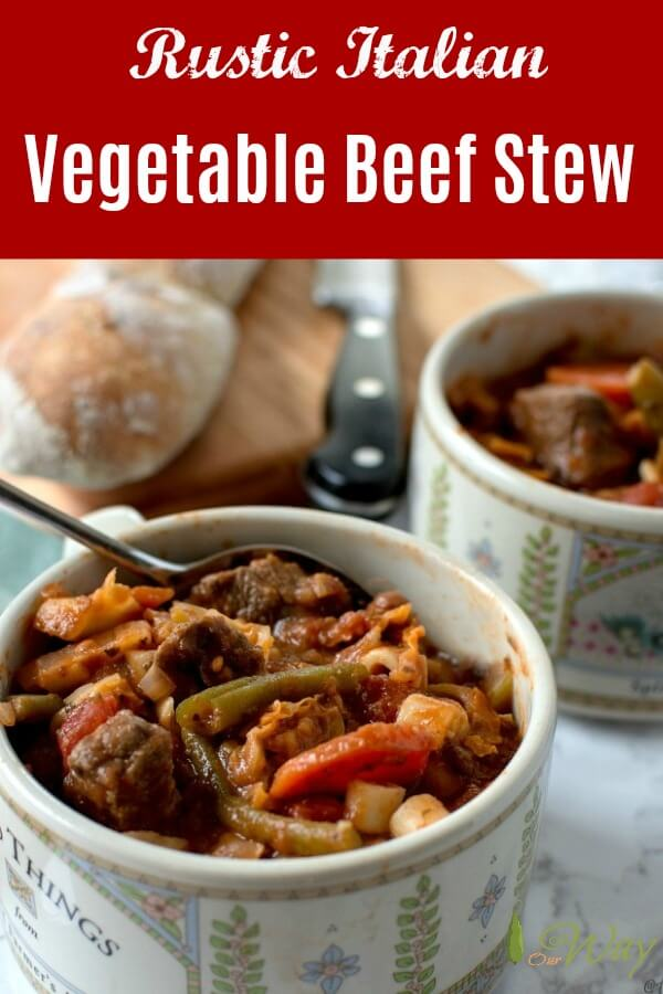 Two bowls filled with vegetable beef stew with spoon sticking out of stew. Baguette on a cutting board with knife.
