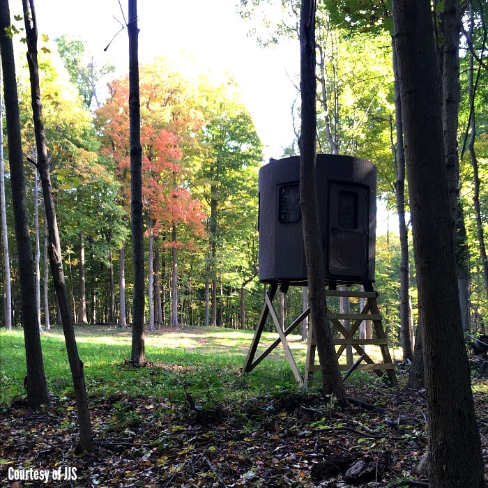 A cylindrical dark brown deer-blind on stilts in the middle of a clearing in the woods with leaves turning colors in autumn.