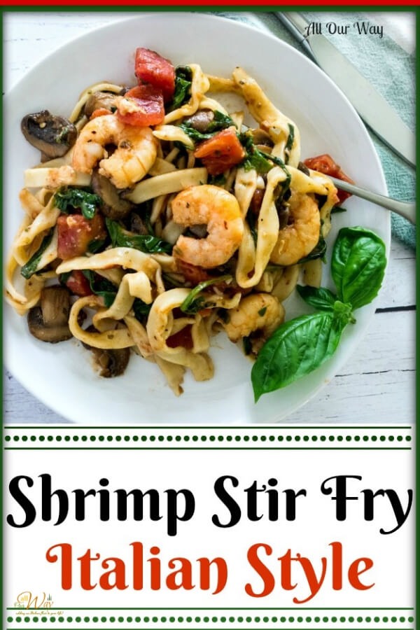 Shrimp stir fry over fettuccini on white dish with basil, tomatoes, and spinach.