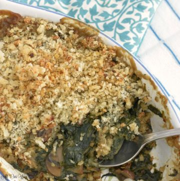 Spoon in a gratin dish filled with spinach gratin and blue floral tea towel on side.
