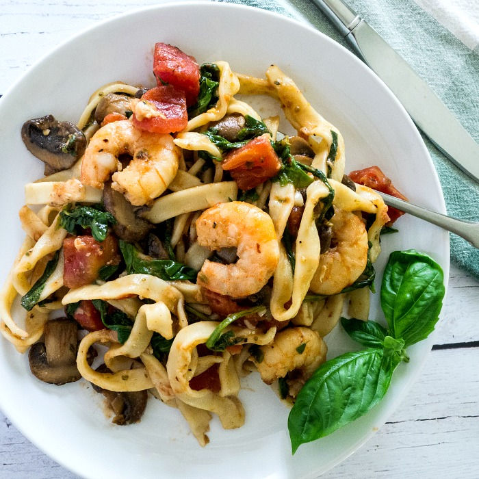 Shrimp Stir Fry Italian Style is a delicious one pan meal served over pasta on a white plate with a green basil sprig on the side. @allourway.com