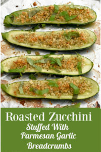 Zucchini boats stuffed with breadcrumbs and sprinkled with basil ribbons on an aluminum covered round baking sheet.