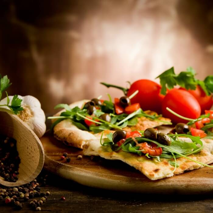 Flatbread made into a pizza with arugula, tomato and olives on top. Bulb of garlic on the side along with a scoop of peppercorns.