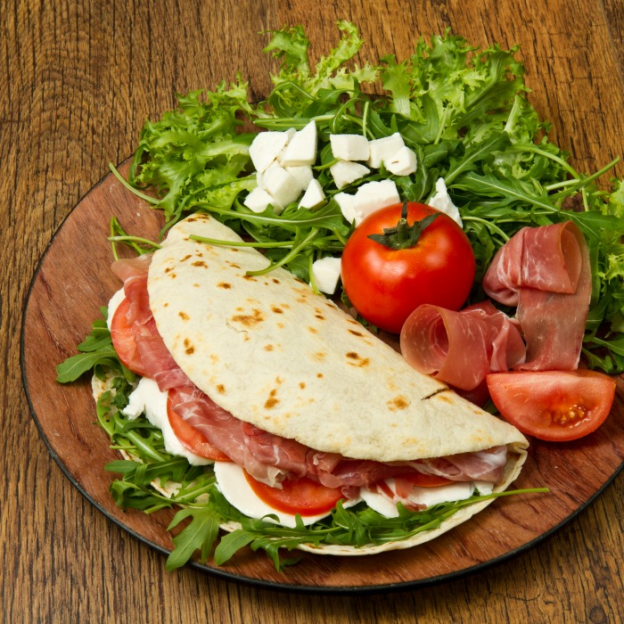 Flatbread folded in half is filled with prosciutto, fresh mozzarella cheese, tomatoes and arugula. All on a wooden server with extra tomato, prosciutto, mozzarella and arugula on the side.