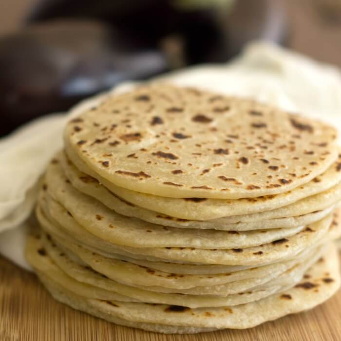 A stack of cooked round flatbread on a wooden cutting board with a white cotton towel in the background.