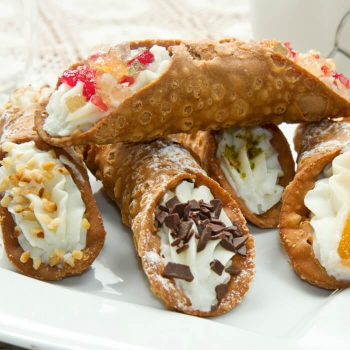 Cannoli Cake with chocolate-dipped strawberries is a variation of the Sicilian pastry.