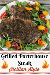 Thick grilled Porterhouse steak on a white plate surrounded by red, yellow, orange, grape tomatoes over green arugula leaves.