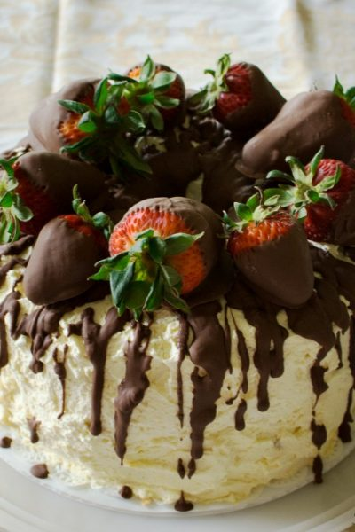 Cannoli cake with whipped cream frosting and chocolate dipped strawberries is variation of the Sicilian classic.