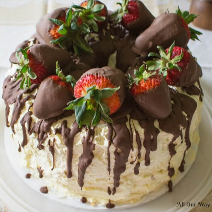 Cannoli Cake filled with sweetened ricotta cheese and chocolate chips and topped with whipped cream and chocolate-dipped strawberries.