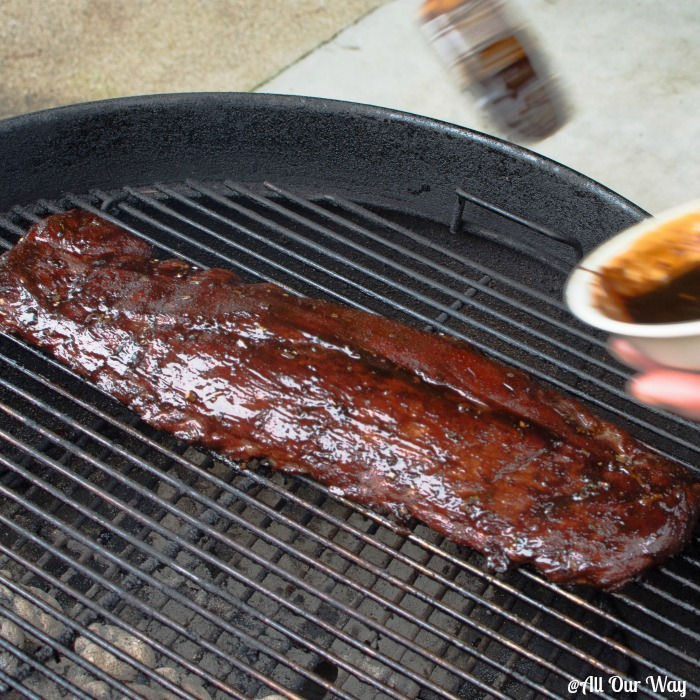 Asian barbecued ribs being basted with a sweet, salty, spicy, sticky sauce.