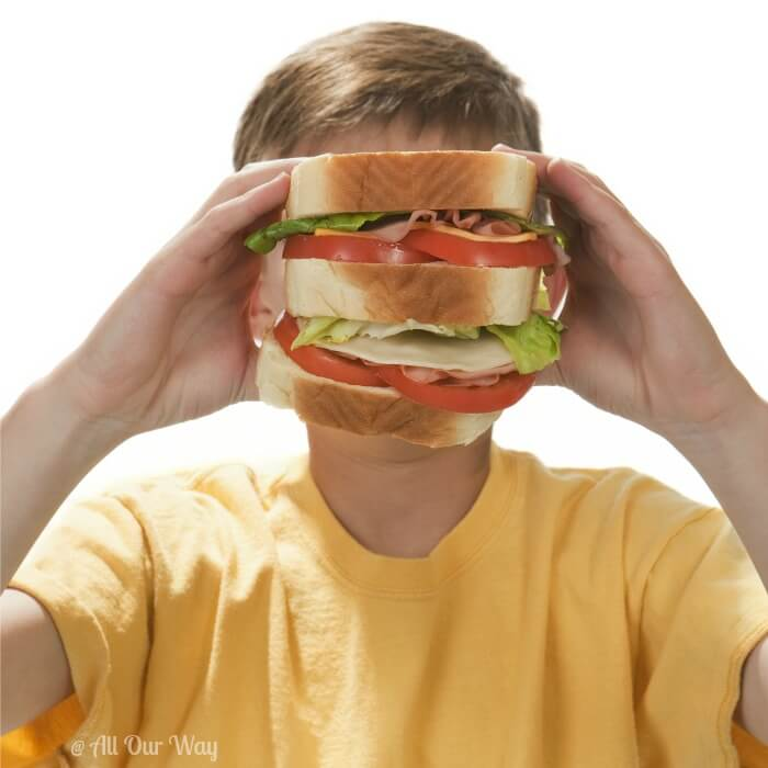 Young boy wearing yellow t-shirt with large sandwich in front of his face.