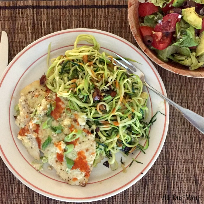 Parmesan Broiled Flounder on a white and brick colored plate with zucchini almond noodles. Plate is on a brown placemat with a wooden bowl filled with a tossed salad.