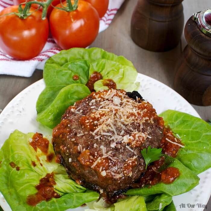 Portabella mushroom caps filled with grilled hamburger on top of lettuce leaves with tomatoes in background.