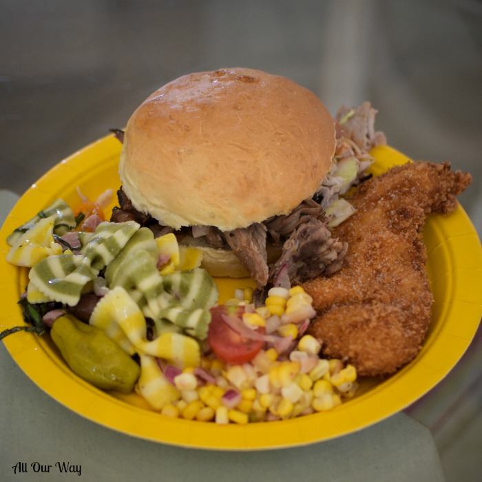 A yellow picnic plate holding pasta salad, corn, fried chicken, and a pulled pork sandwich.