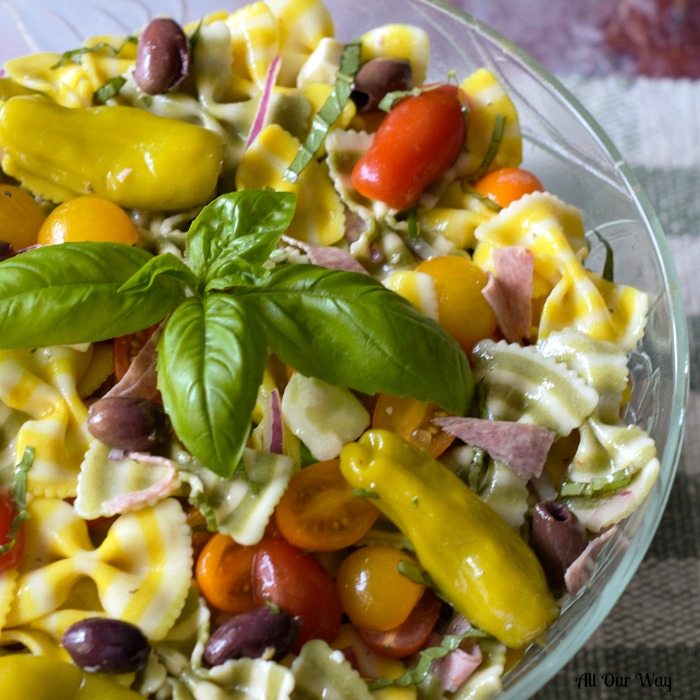 Italian Pasta Salad with striped yellow and green pasta in a glass bowl with tomatoes, black olives, peperoncini.