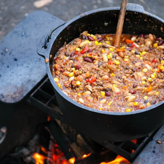 Big cast iron pot over an open fire with Hearty Venison Chili is a modern creation from the Chili con Carne at a campfire.