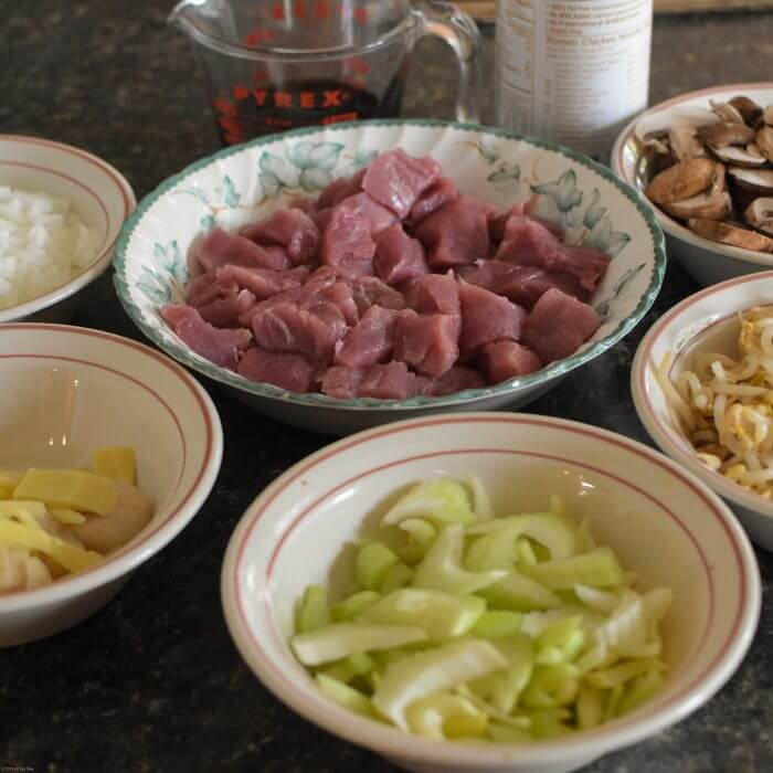 Chop Suey ingredients in bowls for Pork Chop Suey including pork chunks, celery slices, mushroom, onion, bamboo shoots, bean sprouts, soy sauce.