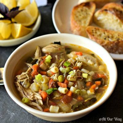 chicken soup in bowl, pasta in soup, lemon wedges, bread for dunking, roasted chicken vegetable soup