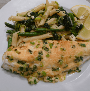Parmesan broiled flounder on plate with pasta and spinach.