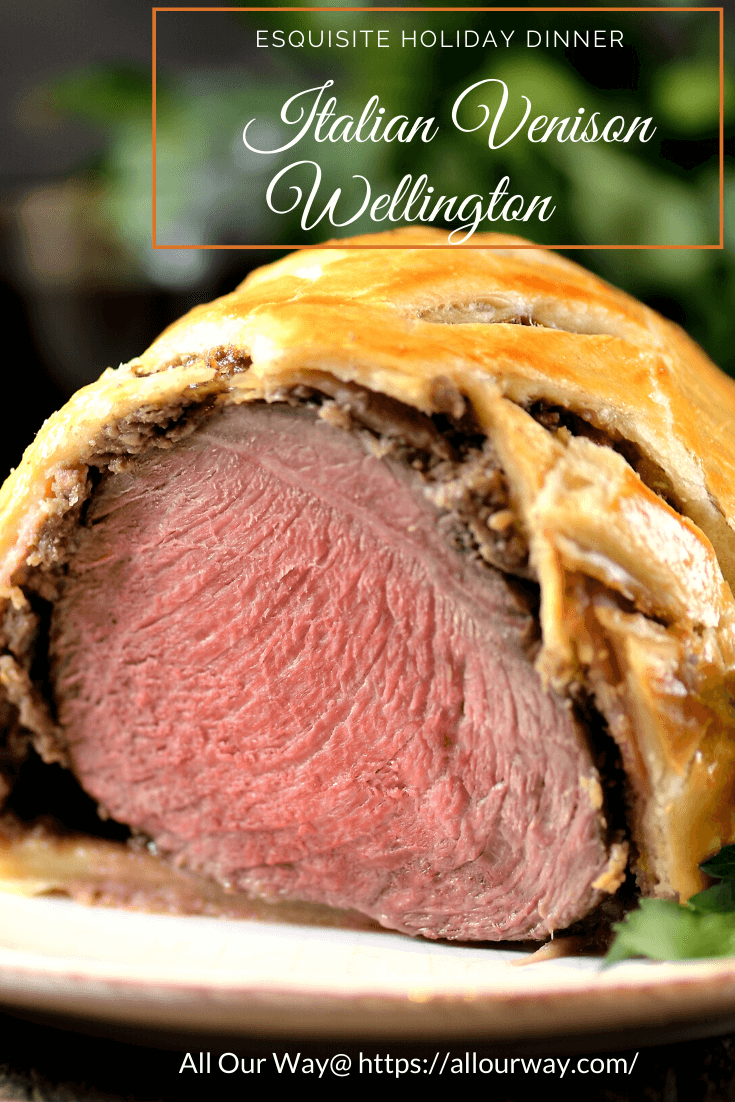Closeup slice of venison Wellington with Christmas greenery in background.
