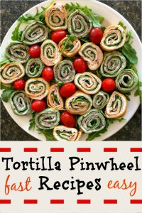 A large white platter filled with colorful spinach and red pepper tortillas and green arugula and grape tomatoes in between the round pinwheels.