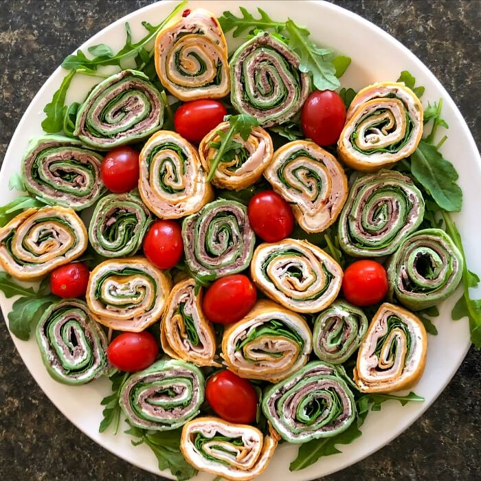 red and green tortilla pinwheels on a white platter with red cherry tomatoes and a sprinkling