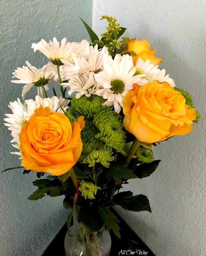 A bouquet of flowers that include yellow roses, white daisy, and mums.