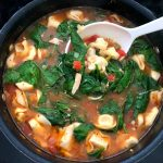 Chicken Spinach Tortellini Soup in large black pot with white spoon stirring in the fresh baby spinach.